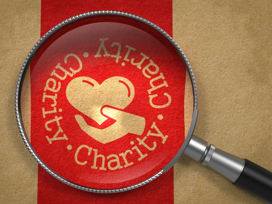 bigstock-Magnifying-Glass-with-Charity--53588929